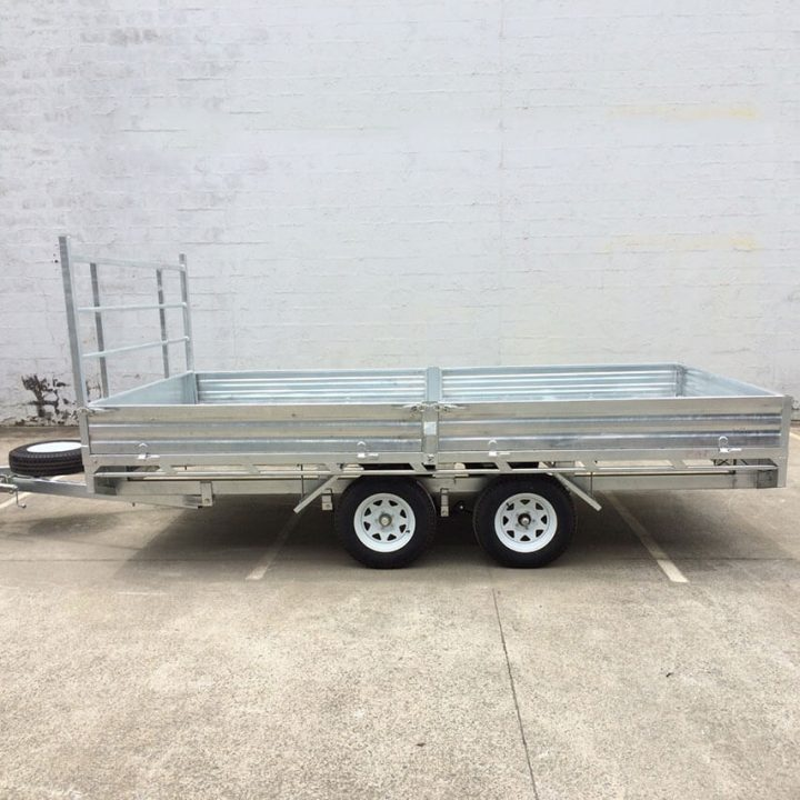 14x7 Flat Top Galvanised Trailer side view in front of building.