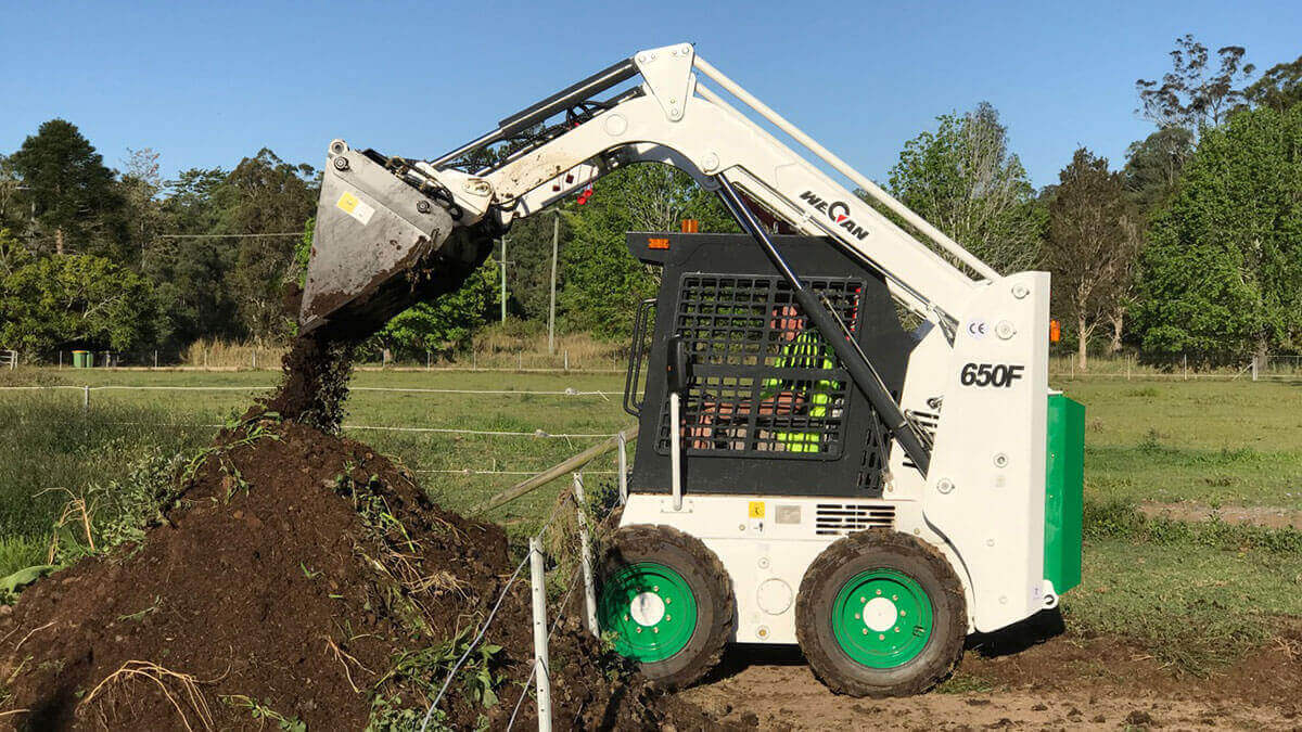 WeCan 650F Skid Steer Loader in use moving dirt.