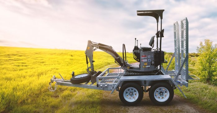Mini excavator on trailer in patch of grass.